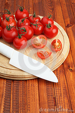 Tomatoes on wooden cutting board being cut in half by white knife