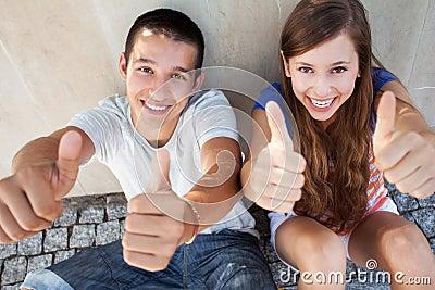 Tonårs- par med tum upp