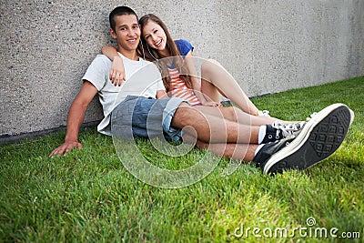 Tonårs- par som sitter på gräs