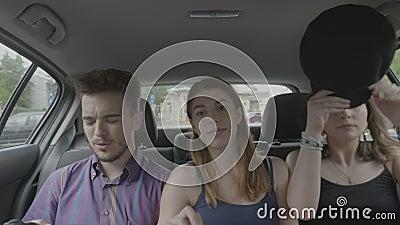 Tonårs- vänner som sitter på passagerareplats inom taxiuberbilen som tycker om ritten till och med staden som tillsammans pratar  stock video