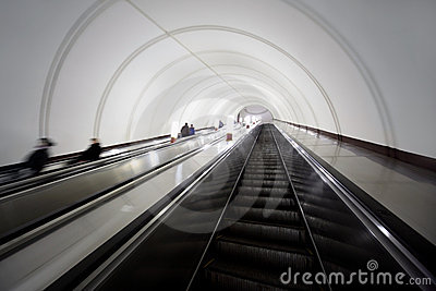Tonnel with escalators, people in motion blur