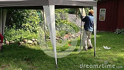 Tonnelle de tente de construction de personnes dans le jardin près de la  maison rurale de ferme.