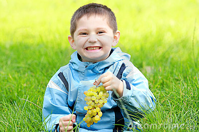 Toothy smiling boy with grapes