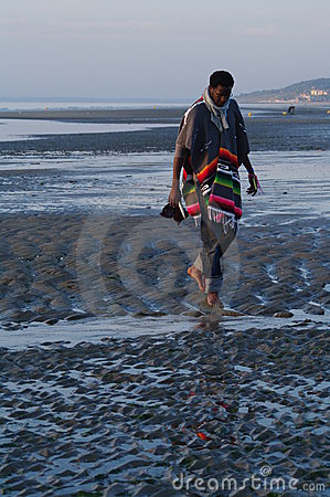 Top model in poncho walking on sandy strange beach