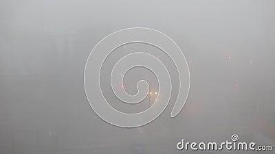 Top shot van de auto die door een kruispunt met zwaar mist rijdt stock videobeelden