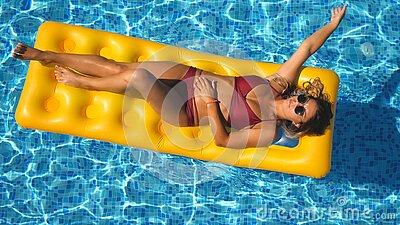 Top view of beautiful tanned girl in sunglasses and red bikini lying on yellow inflatable mattress in swimming pool. Young woman relaxing in basin of hotel stock video