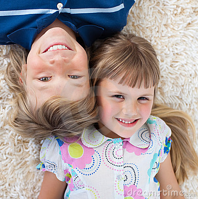Top view of brother and sister lying on the floor