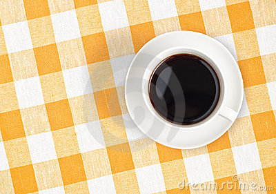Top view of coffee cup on checked tablecloth
