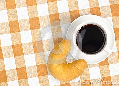Top view coffee cup and croissant on tablecloth