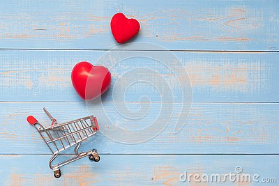 couple red heart shape with mini shopping cart on blue pastel wooden table. love, shopping and Valentine Day Concept Stock Photo