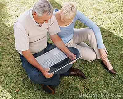Top view of a couple using laptop on grass