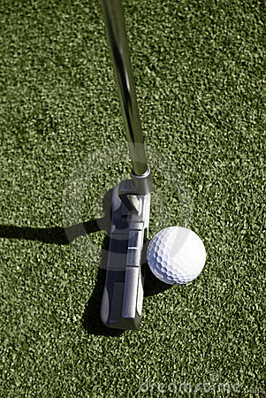 Top view of golf ball and putter behind ball