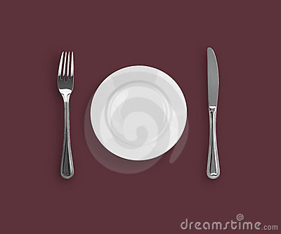Top view of knife, plate and fork on purple