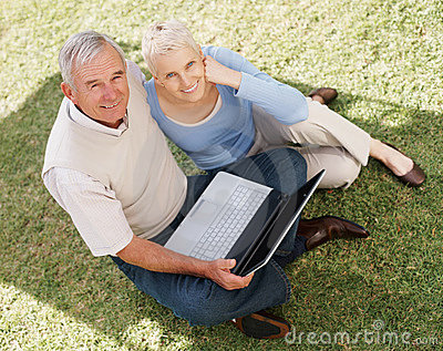 Top view of a senior couple using laptop on grass