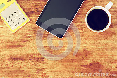 Top view of tablet, coffee cup and calculator over wooden textured table background.