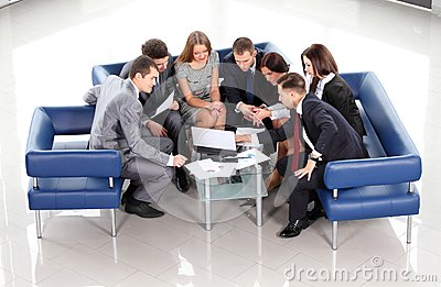Working business group sitting at table during corporate meeting