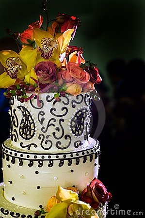 Top of wedding cake topped with bright flowers