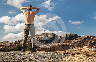 Topless man relaxed stands on the mountain