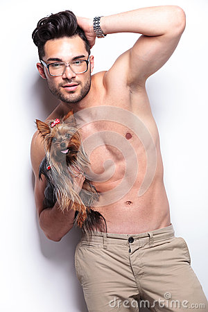 Topless young man holds puppy while posing