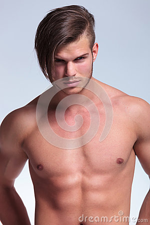 Topless young man stands with hands at back