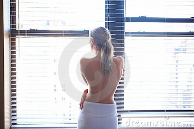 Topless young woman looking out of window