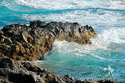 Torcoiuse waves break on black lava rocks