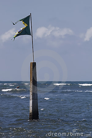 Torn flag on marker in sea
