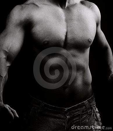 Torso of muscular shirtless man in the dark