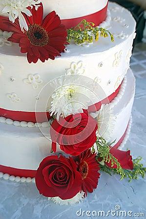 Torta de boda con las rayas y las flores rojas