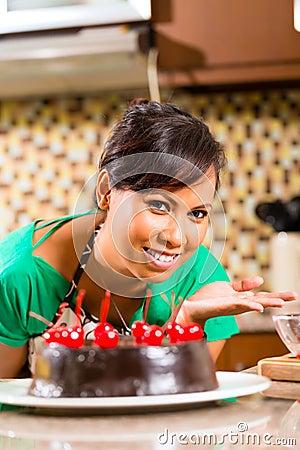 Torta de chocolate asiática de hornada de la mujer en cocina