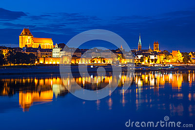 Torun old town at night reflected in Vistula river