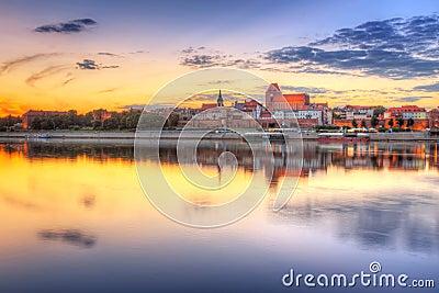 Torun old town reflected in Vistula river at sunset