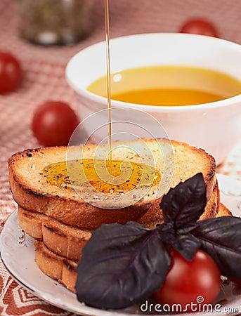 Tostadas, aceite de oliva, hierba de la albahaca y tomates