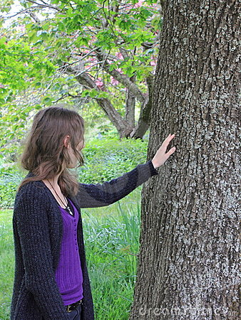 Woman touching oak tree