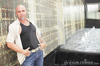 Tough guy leaning on a wall