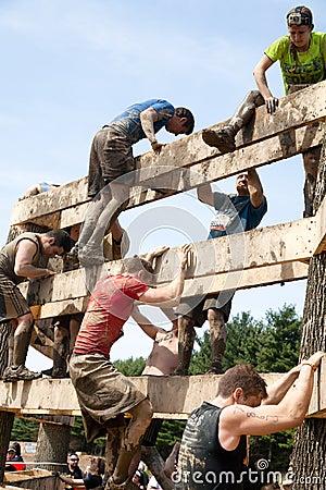 Tough Mudder: Racers Climbing the Wall Editorial Photo