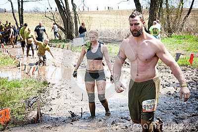 Tough Mudder: Racers Walking through Mud Editorial Stock Image