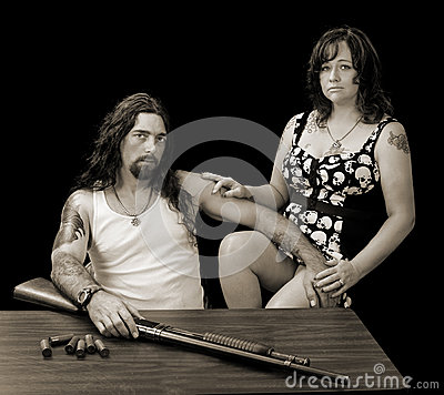 Tough man with tough woman and a shotgun with shellson