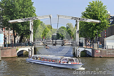 Tour boat in the Amsterdam canal belt. Editorial Photo