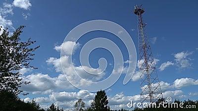 Tour cellulaire de communications avec des nuages dans le jour d'été Tour de transmission de signal sur l'endroit scénique Plein  banque de vidéos