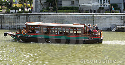 Tourist boat exploring Singapore from riverside Editorial Stock Image