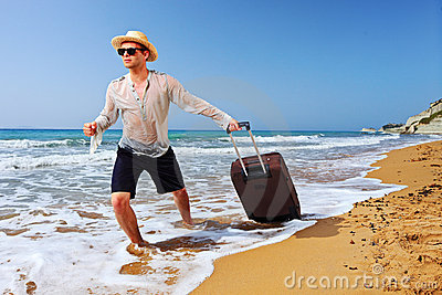 A tourist carrying a suitcase at the beach