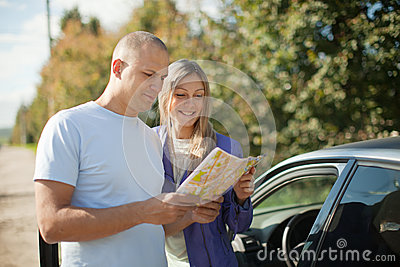 Tourist couple looking at the map on the road