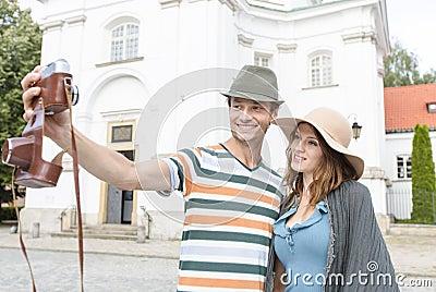 Tourist couple taking self portrait outside St. Casimir Church, Warsaw, Poland