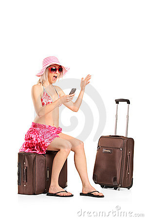 Tourist girl seated on a suitcase shouting