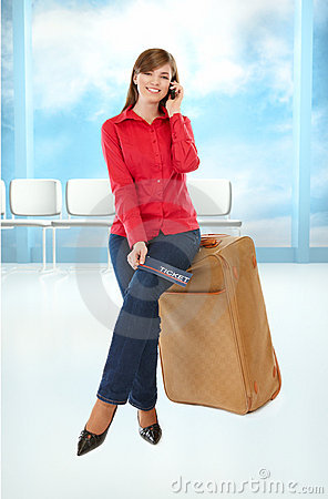 Tourist girl sitting on a suitcase