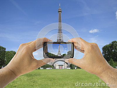 Tourist holds up camera phone at   eiffel tower