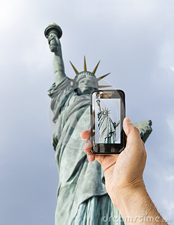 Tourist holds up camera phone at  statue of libert