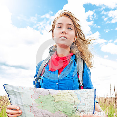 Tourist with map in summer field.