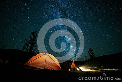 Tourist near his camp tent at night. Stock Photo